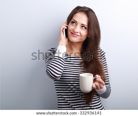Happy casual thinking woman talking on mobile phone and holding cup of tea and looking up on blue background - stock photo