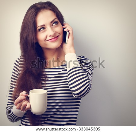 Happy casual thinking woman talking on mobile phone and holding cup of tea. Vintage closeup portrait - stock photo
