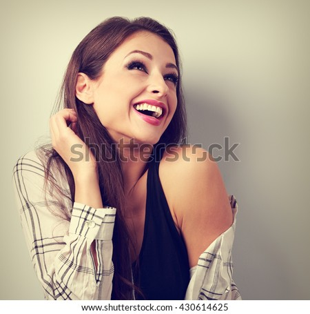 Happy casual toothy laughing woman in shirt looking up. Toned vintage closeup portrait