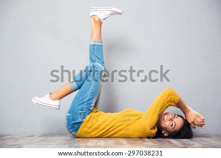 Happy casual woman lying on the floor with raised legs up over gray background and looking at camera - stock photo