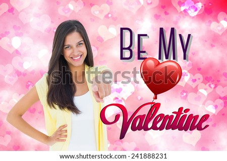 Happy casual woman pointing to camera against digitally generated girly heart design - stock photo