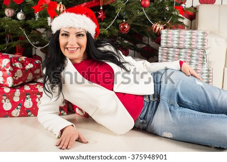 Happy casual woman with Santa hat lying in front of Christmas tree with gifts - stock photo