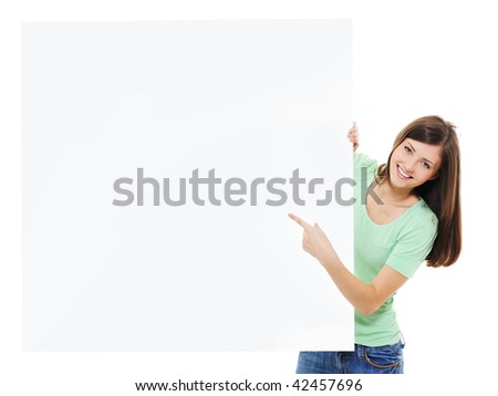 Happy casual young female show on the message on blank billboard - stock photo