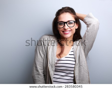 Happy casual young woman in glasses looking on blue background - stock photo