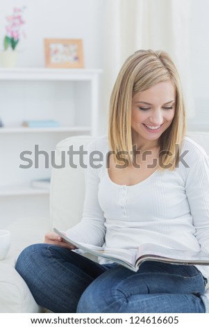 Happy casual young woman reading magazine on couch at home - stock photo