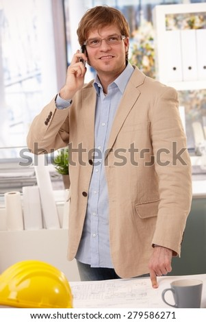 Happy caucasian architect talking on phone at office pointing at table. Wearing glasses, looking up, hardhat. - stock photo