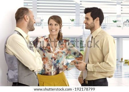 Happy caucasian business people chatting at high tech bright office lobby. Suit, no jacket, smiling, - stock photo