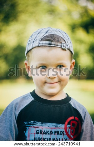 Happy Caucasian Child Boy Smiling Outdoors With Stripped Cap, Green Nature Background - stock photo