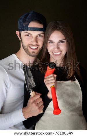 Happy Caucasian couple holding hand tools - stock photo
