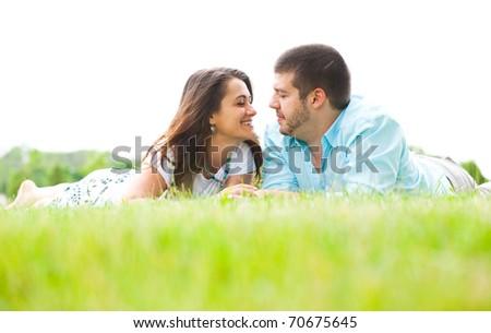 Happy caucasian couple lying in grass - stock photo