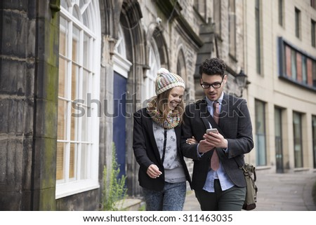 Happy Caucasian couple walking down the street using a Smart Phone. Young man and woman walking together. - stock photo
