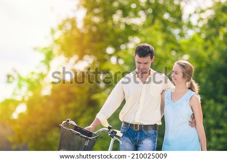 Happy Caucasian Couple Walking in Park Area With Bicycle Outdoors. Emotional Portrait. Horizontal Image - stock photo