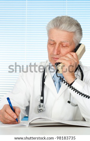 Happy Caucasian doctor with a telephone sitting on a light background - stock photo