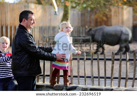 Happy caucasian family, active father with two blonde children, laughing boy and his toddler sister having fun together watching animals on a day trip to the zoo park during weekend - stock photo