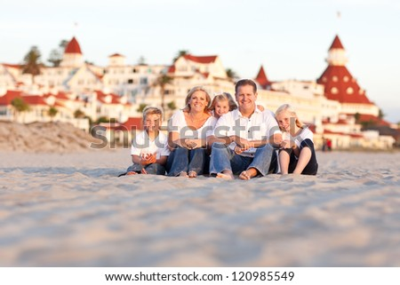 Happy Caucasian Family in Front of Hotel Del Coronado, U.S.A. on a Sunny Afternoon. - stock photo