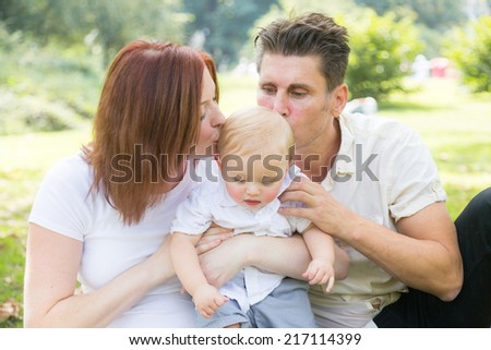 Happy caucasian family portrait at park in New York. Father and mother with a baby child, they are kissing him on the head. Love and lifestyle concepts.  - stock photo