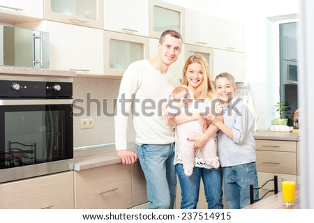 Happy caucasian family with teenage son and baby girl standing in kitchen together and smiling at viewer - stock photo