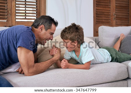 happy caucasian father and son kid competing in arm wrestling while both lying on the sofa