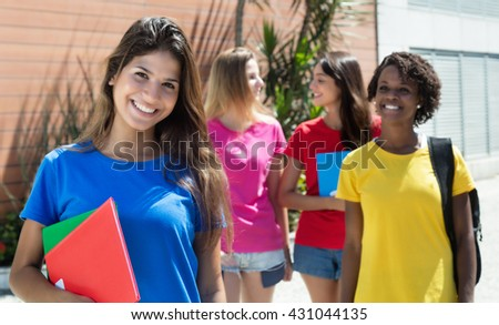 Happy caucasian female student in red shirt with other international students - stock photo