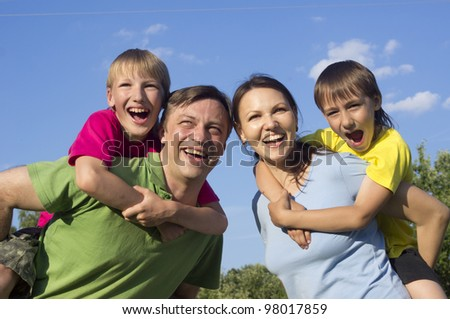 Happy Caucasian good mother and father together with his sons play the fool on the street
