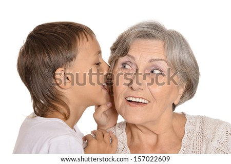 Happy Caucasian grandmother and her grandson fooled on a light background - stock photo