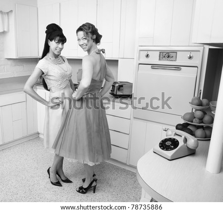 Happy Caucasian housewives in a retro kitchen with hand on hips - stock photo
