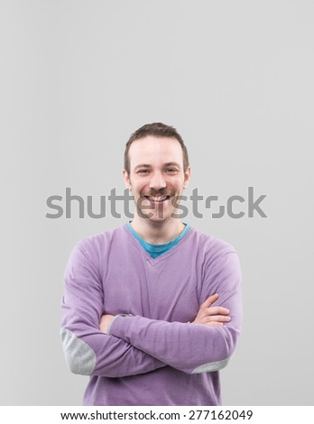 happy caucasian man standing with crossed arms against his chest, on grey background - stock photo