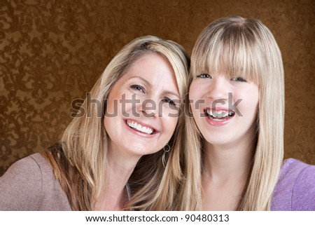 Happy Caucasian mom and daughter smile over green background - stock photo