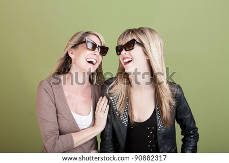 Happy Caucasian mom and daughter with sunglasses laugh together - stock photo