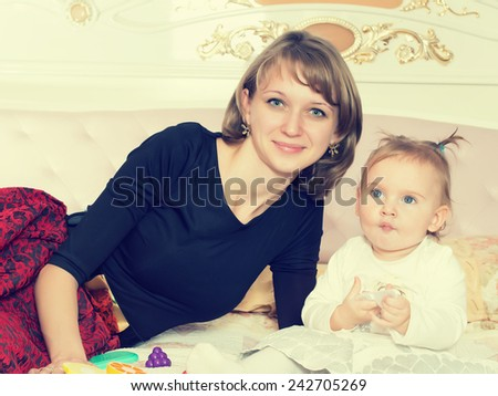 Happy caucasian mother and daughter on the bed at home
