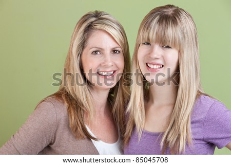Happy Caucasian mother and daughter smile over green background - stock photo