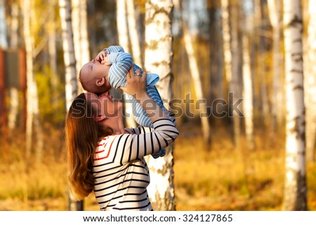 Happy Caucasian mother and son outdoors in park on sunny autumn day. Young mother lifting her son in park having fun enjoying motherhood. - stock photo