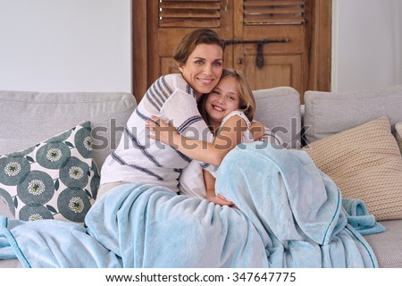 happy caucasian mother hugging cuddling her daughter sitting on the coach all snuggled with a blanket love - stock photo