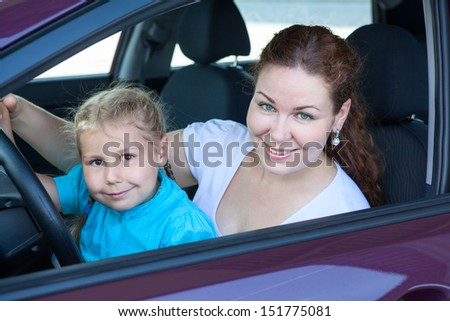 Happy Caucasian mother with small daughter sitting together on driver seat inside of car - stock photo