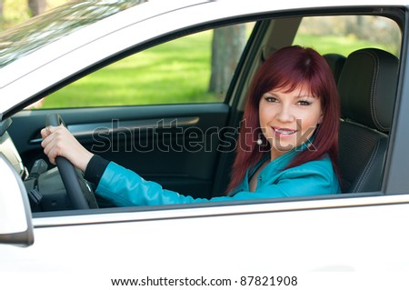 Happy caucasian redheaded woman sitting behind the wheel of her car, smiling and looking at camera - stock photo