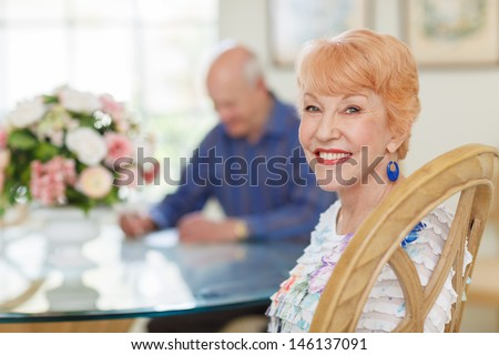 Happy caucasian Senior Couple in Dining room. Female sitting looking at camera. Senior husband out of focus looking at papers at table. Bright and Airy. - stock photo