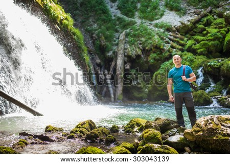 Happy caucasian tourist with camera near a waterfall - stock photo