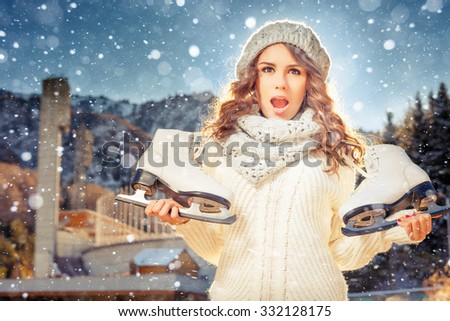 Happy caucasian woman going to ice skating outdoor. She dressed in white winter pullover and warm hat. Holding skates shoes. Healthy lifestyle and sport concept at olympic stadium, mountain landscape - stock photo