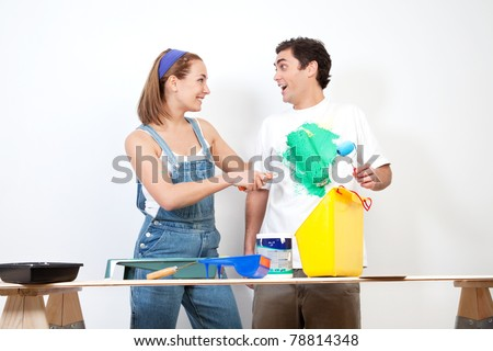 Happy Caucasian woman having fun coloring her boyfriend's shirt