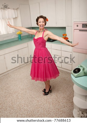 Happy Caucasian woman in a retro styled kitchen scene - stock photo