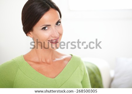 Happy caucasian woman in green shirt looking at the camera while smiling at indoors - copy space - stock photo