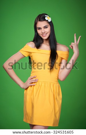 Happy caucasian woman in summer yellow dress showing two fingers, V sign - stock photo