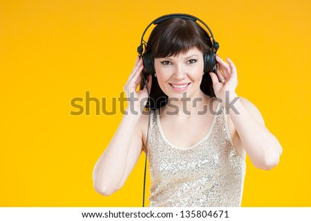 Happy caucasian woman listening to music in headphones, studio shot - stock photo