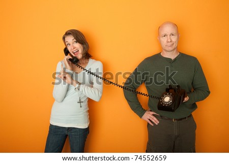 Happy Caucasian Woman on telephone conversation with bored man - stock photo