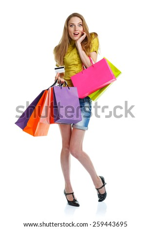 Happy caucasian woman with shopping bags and holding credit card on white background. Holidays concept - stock photo