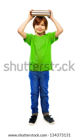 Happy Caucasian 9 years old boy in green shirt holding stack of books on top of head portrait, full height portrait, isolated on white - stock photo