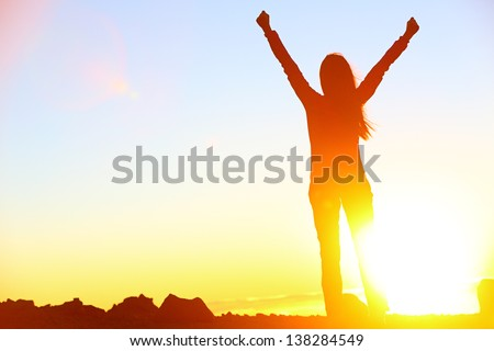 Happy celebrating winning success woman at sunset or sunrise standing elated with arms raised up above her head in celebration of having reached mountain top summit goal during hiking travel trek. - stock photo