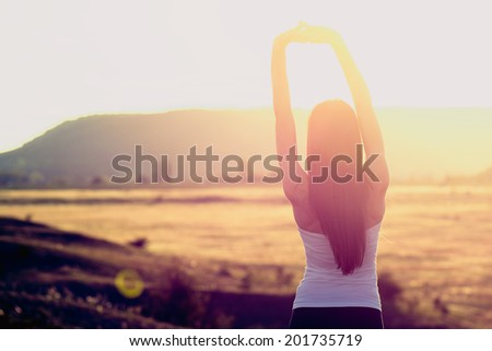 Happy celebrating winning success woman at sunset or sunrise standing elated with arms raised up above her head - stock photo