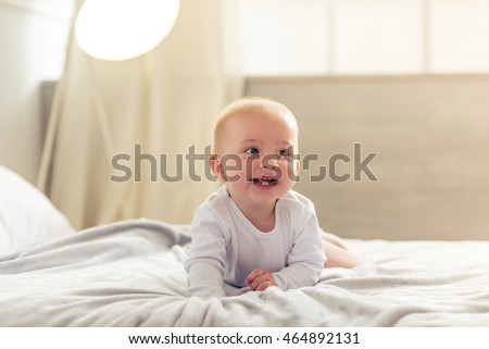 Happy charming baby is looking away and smiling while crawling on the bed at home