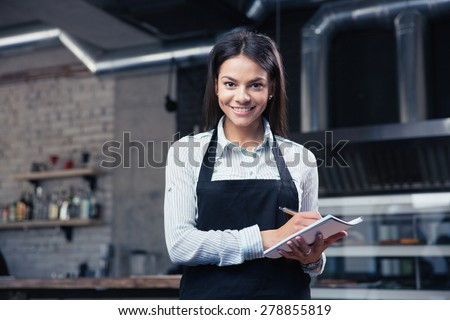 Happy charming female waiter in apron writing order and looking at camera - stock photo